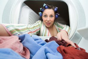 a woman reaching in the dryer for clothes - domestic series