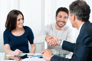 Happy couple seal a deal with their personal financial advisor a